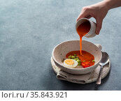 Hand pouring of Gaspacho soup in bowl. Стоковое фото, фотограф Ольга Сергеева / Фотобанк Лори