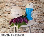 Сиреневый букет и женская шляпка на стуле. Стоковое фото, фотограф Евгений Будюкин / Фотобанк Лори