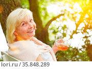 Glückliche Senioren trinkt Tee im Sommer zur Entspannung im Garten. Стоковое фото, фотограф Zoonar.com/Robert Kneschke / age Fotostock / Фотобанк Лори
