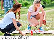 Zwei junge Frauen als ehrenamtliche Aktivisten malen zusammen ein... Стоковое фото, фотограф Zoonar.com/Robert Kneschke / age Fotostock / Фотобанк Лори
