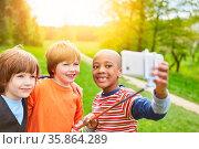 Drei Jungs machen zusammen ein Selfie mit Smartphone in der Natur. Стоковое фото, фотограф Zoonar.com/Robert Kneschke / age Fotostock / Фотобанк Лори