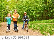 Drei Kinder mit Roller und Fahrrad machen zusammen einen Ausflug ... Стоковое фото, фотограф Zoonar.com/Robert Kneschke / age Fotostock / Фотобанк Лори