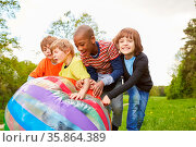 Lachende Kinder rollen zusammen einen bunten Ball über eine Wiese... Стоковое фото, фотограф Zoonar.com/Robert Kneschke / age Fotostock / Фотобанк Лори
