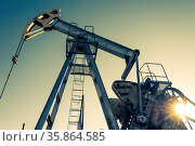 Oil pumpjack, industrial equipment on sunset sky background. Rocking... Стоковое фото, фотограф Zoonar.com/BASHTA / easy Fotostock / Фотобанк Лори
