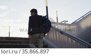 Asian man with backpack climbing up the stairs at corporate park. Стоковое видео, агентство Wavebreak Media / Фотобанк Лори