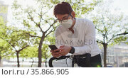 Asian man wearing face mask using smartphone while leaning on his bicycle on the street. Стоковое видео, агентство Wavebreak Media / Фотобанк Лори