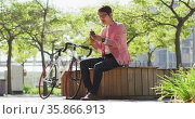 Asian man having a snack and using smartphone while sitting at the park. Стоковое видео, агентство Wavebreak Media / Фотобанк Лори
