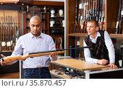 Latin american man choosing hunting break barrel shotgun in shop. Стоковое фото, фотограф Яков Филимонов / Фотобанк Лори