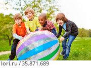 Vier Kinder als Freunde rollen zusammen eine bunten Ball im Park ... Стоковое фото, фотограф Zoonar.com/Robert Kneschke / age Fotostock / Фотобанк Лори