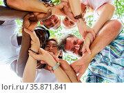 Junge Leute im Kreis mit verschränkten Händen als Zeichen für Netzwerk... Стоковое фото, фотограф Zoonar.com/Robert Kneschke / age Fotostock / Фотобанк Лори