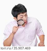 Young man looking through magnifying glass. Стоковое фото, агентство Ingram Publishing / Фотобанк Лори
