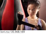 Young confident female boxer wrapper her wrists in the gym . Стоковое фото, агентство Ingram Publishing / Фотобанк Лори
