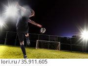 Athlete kicking soccer ball into a goal. Стоковое фото, агентство Ingram Publishing / Фотобанк Лори