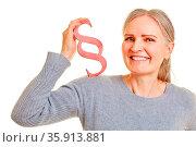 Ältere Frau hält einen roten Paragraph als Recht und Gesetz Symbol. Стоковое фото, фотограф Zoonar.com/Robert Kneschke / age Fotostock / Фотобанк Лори