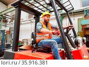 Arbeiter als Gabelstaplerfahrer auf dem Gabelstapler in der Fabrik... Стоковое фото, фотограф Zoonar.com/Robert Kneschke / age Fotostock / Фотобанк Лори