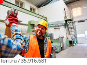 Handwerker begrüßt einen Kollegen in der Fabrik mit High Five für... Стоковое фото, фотограф Zoonar.com/Robert Kneschke / age Fotostock / Фотобанк Лори