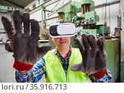 Arbeiter mit VR-Brille greift mit Händen bei Virtual Reality Simulation... Стоковое фото, фотограф Zoonar.com/Robert Kneschke / age Fotostock / Фотобанк Лори