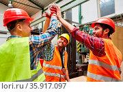 Gruppe Handwerker und Arbeiter beim High Five für Team Motivation... Стоковое фото, фотограф Zoonar.com/Robert Kneschke / age Fotostock / Фотобанк Лори