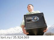 Man carrying safe near mountains. Стоковое фото, фотограф Shannon Fagan / Ingram Publishing / Фотобанк Лори