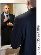 Man adjusting his tie in mirror. Стоковое фото, фотограф Shannon Fagan / Ingram Publishing / Фотобанк Лори