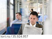 Businessman reading newspaper on train. Стоковое фото, фотограф Shannon Fagan / Ingram Publishing / Фотобанк Лори