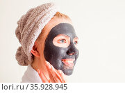 Happy woman appling a black face mask over white background. Skincare... Стоковое фото, фотограф Zoonar.com/Oksana Shufrych / easy Fotostock / Фотобанк Лори