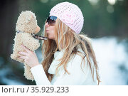 Woman blowing kisses to scruffy teddy bear in a snow covered winter... Стоковое фото, фотограф Zoonar.com/Leah-Anne Thompson / easy Fotostock / Фотобанк Лори