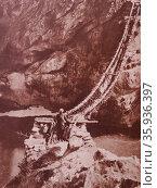 Rope bridge across a river in Kashmir India 1930. Редакционное фото, агентство World History Archive / Фотобанк Лори