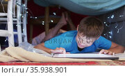 Caucasian boy smiling while using digital tablet under the blanket fort at home. Стоковое видео, агентство Wavebreak Media / Фотобанк Лори