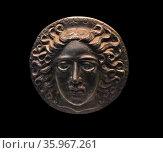 Greek bronze disc, with a head of the sun-god Apollo Helios. 5th-3rd century BC. Редакционное фото, агентство World History Archive / Фотобанк Лори