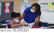 Diverse female teacher helping schoolgirl with lesson, all wearing face masks. Стоковое видео, агентство Wavebreak Media / Фотобанк Лори