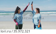 Two diverse women wearing volunteer t shirts and face masks picking up rubbish from beach. Стоковое видео, агентство Wavebreak Media / Фотобанк Лори