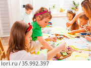 Little boys and gilrs do applique work together in a masterclass. Стоковое фото, фотограф Zoonar.com/Oksana Shufrych / easy Fotostock / Фотобанк Лори