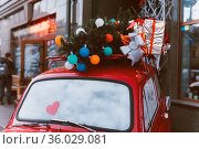 Red retro car with a Christmas tree fir tied to the roof, family celebration... Стоковое фото, фотограф Zoonar.com/Oleksii Hrecheniuk / easy Fotostock / Фотобанк Лори