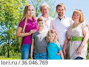 Multigeneration family portrait outdoors. Happy parents with two children... Стоковое фото, фотограф Zoonar.com/Ivan Mikhaylov / easy Fotostock / Фотобанк Лори