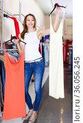 young satisfied brunette selecting new dress in fashionable showroom. Стоковое фото, фотограф Яков Филимонов / Фотобанк Лори