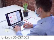 Caucasian businessman wearing face mask sitting at desk in office using laptop. Стоковое фото, агентство Wavebreak Media / Фотобанк Лори
