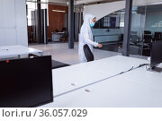 Cleaner wearing ppe suit, glasses and mask disinfecting office workspace. Стоковое фото, агентство Wavebreak Media / Фотобанк Лори