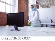 Cleaner wearing ppe suit, glasses and mask disinfecting office workspace, spraying desks. Стоковое фото, агентство Wavebreak Media / Фотобанк Лори