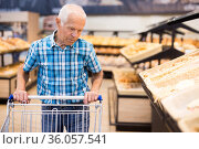 elderly man buying bread and pastries in grocery section of the supermarket. Стоковое фото, фотограф Татьяна Яцевич / Фотобанк Лори