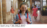 Portrait of happy caucasian schoolgirl standing in corridor looking at camera. Стоковое видео, агентство Wavebreak Media / Фотобанк Лори