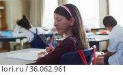 Portrait of happy caucasian schoolgirl sitting at classroom, making notes, looking at camera. Стоковое видео, агентство Wavebreak Media / Фотобанк Лори