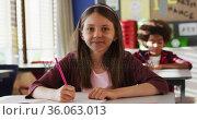 Portrait of caucasian schoolgirl sitting in class, making notes, looking at camera. Стоковое видео, агентство Wavebreak Media / Фотобанк Лори