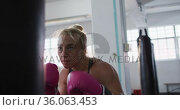 Caucasian female boxer wearing boxing gloves training with punching bag at the gym. Стоковое видео, агентство Wavebreak Media / Фотобанк Лори