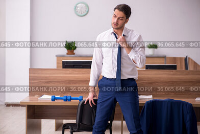 Young businessman employee doing sport exercises at workplace
