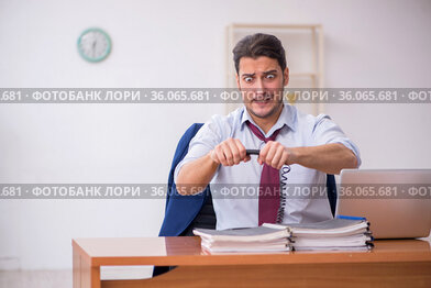 Young businessman and too much work in the office