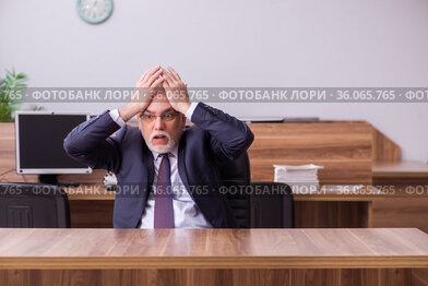 Old businessman employee sitting in the office