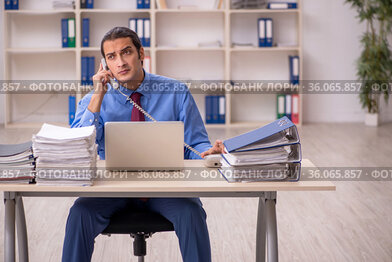 Young male employee unhappy with excessive work