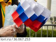 Волонтеры раздают защитные маски и флажки с российским триколором во время праздничного мероприятия, посвященного Дню России, на ВДНХ в городе Москве, Россия 20 июня 2021. Редакционное фото, фотограф Николай Винокуров / Фотобанк Лори