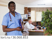 Portrait of a positive african american doctor in a clinic, standing in a office. Стоковое фото, фотограф Яков Филимонов / Фотобанк Лори